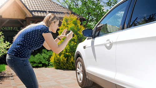 Woman taking picture of car